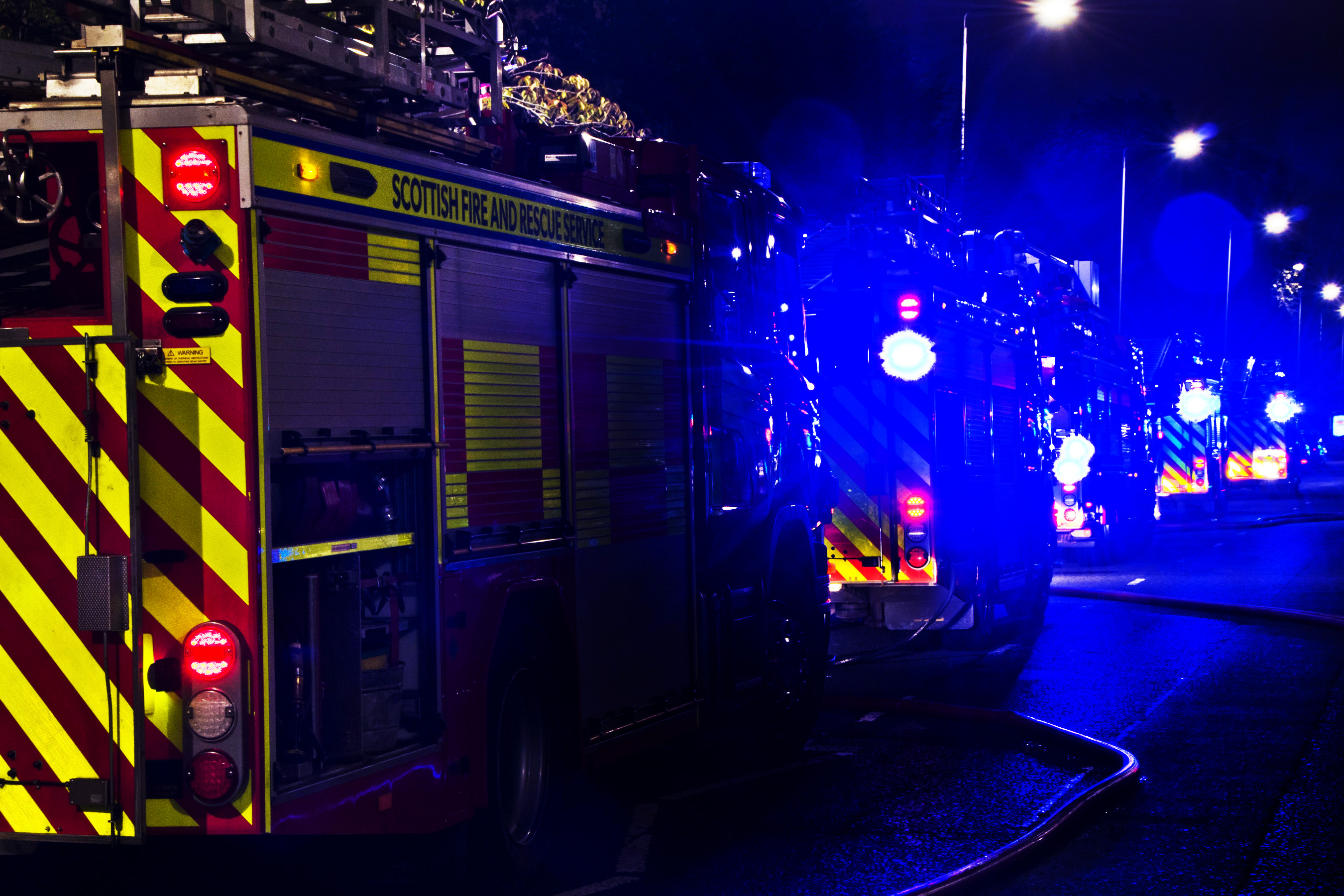 Line of fire engines, blue lights, appliances, night